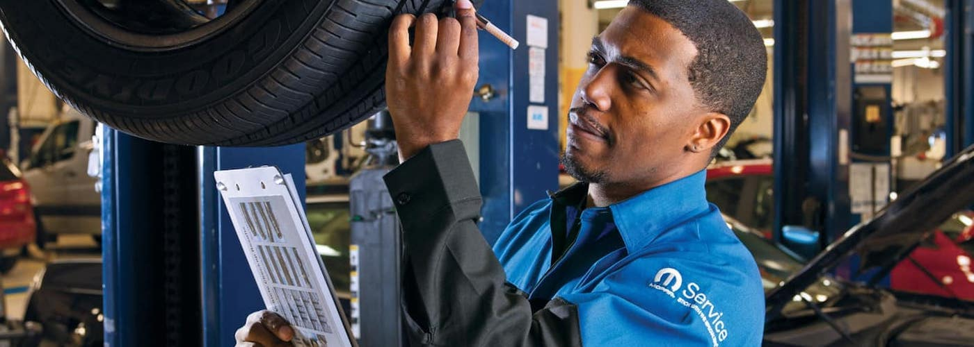 A technician at a Dodge and Ram service department inspects a car