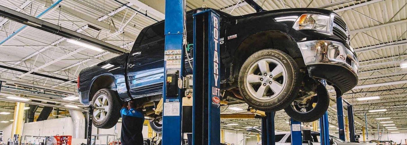 A technician at a local dealer doing a brake service on a blue truck