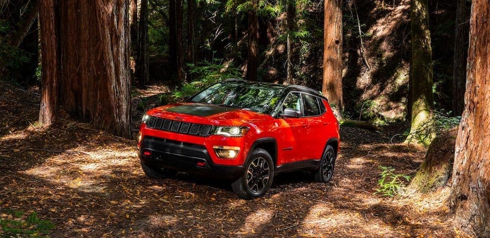 A red Jeep Compass, popular among used SUVs for sale, is driving in the woods near Colorado Springs, CO.