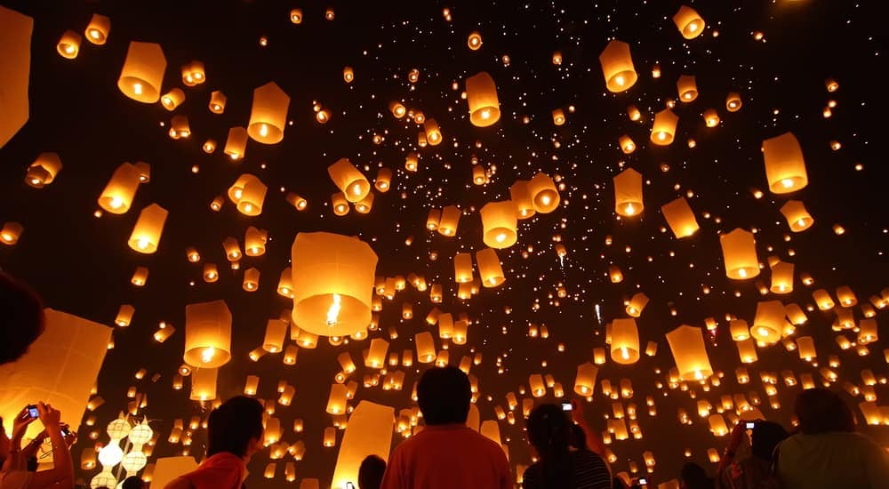 Hundreds of lanterns are floating in the dark sky.