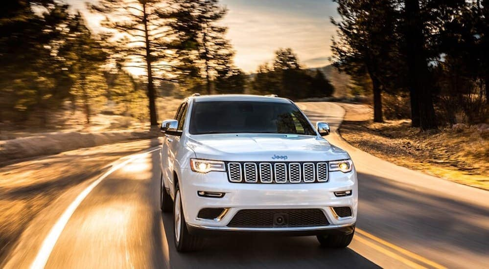 A white 2017 Jeep Grand Cherokee, popular among used car in Colorado Springs, CO, is driving on a highway with trees close by.