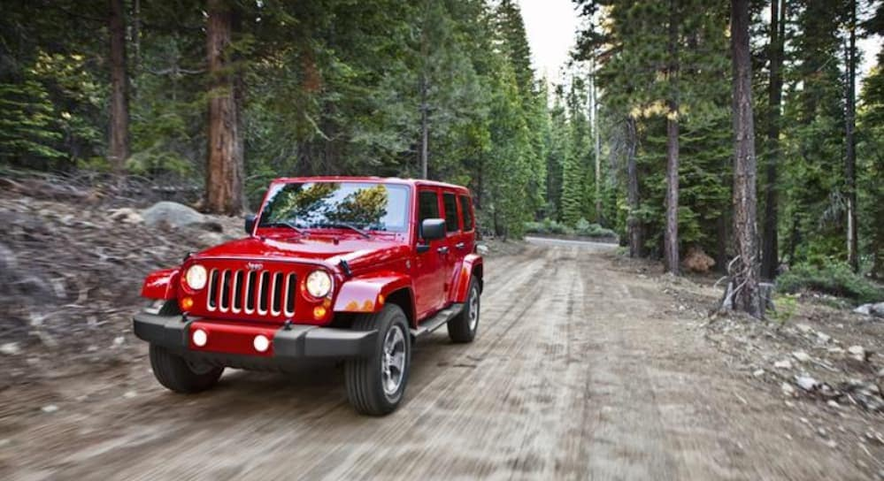 A red 2017 Jeep Wrangler, which is popular among used car in Colorado Springs, CO, is driving on a dirt backroad.