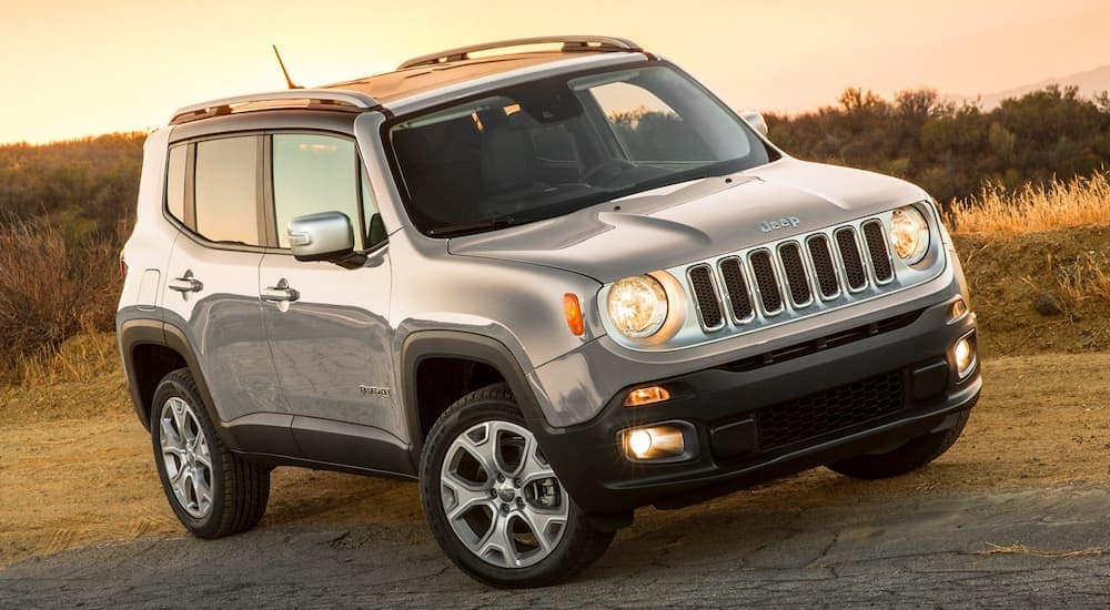 A silver 2018 Jeep Renegade, popular among used cars in Colorado Springs, CO, is parked in front of a grassy field.