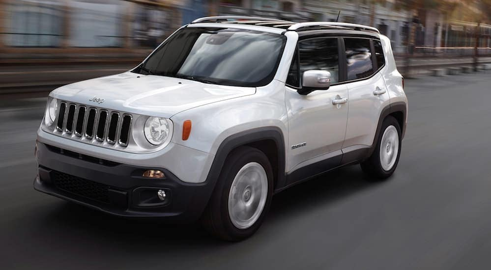 A white 2018 Jeep Renegade, a favorite among used cars in Colorado Springs, CO, is driving on a street.