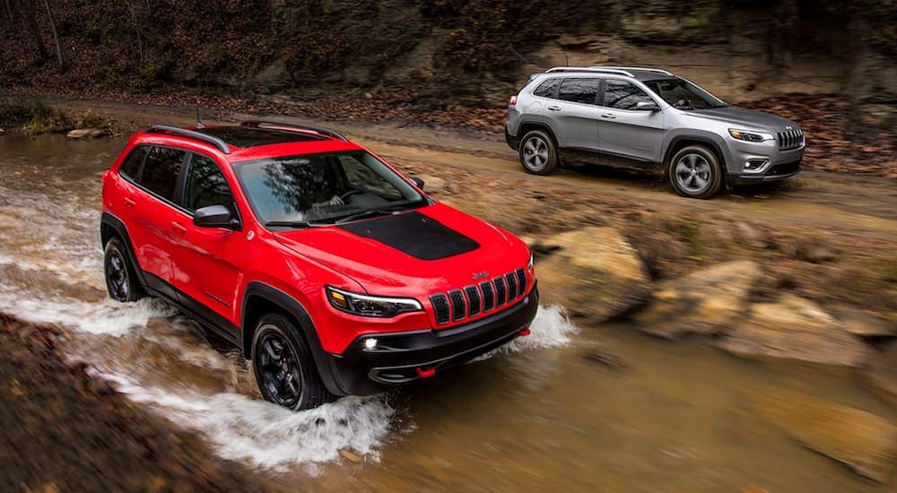 A red 2019 Jeep Cherokee is driving in a river while a grey one drives on the trail.