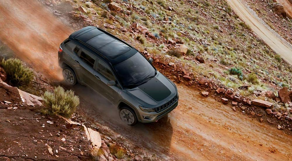A dark grey 2019 Jeep Compass is shown from above on a dirt road.