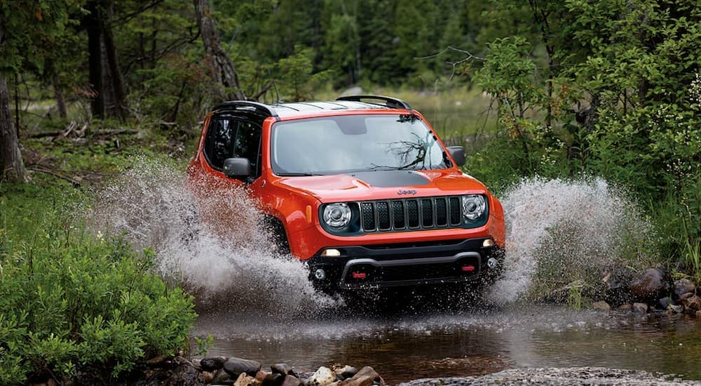 An orange 2019 Jeep Renegade, popular among Jeeps for sale in Colorado Springs, is splashing through a river.
