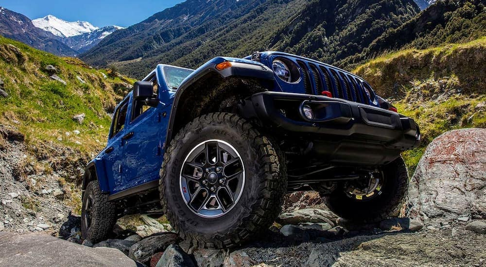 A blue 2019 Jeep Wrangler is posing on a rocky trail in the mountains.