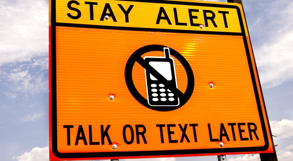 "A traffic sign that says, ""Stay Alert. Talk or Text Later""."