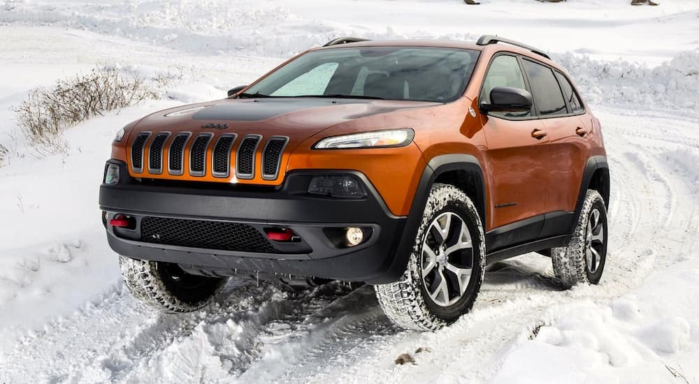 When asking 'what are the best used SUVs in Colorado Springs?' this orange 2015 Jeep Cherokee in the snow might be a result.