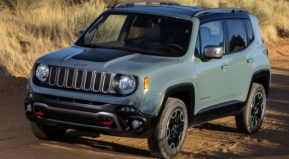 A blue 2016 Jeep Renegade is driving on a dirt road.