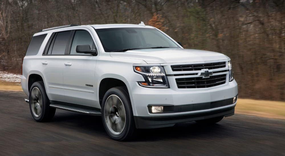 A white 2018 Chevy Tahoe is driving past trees with no leaves.