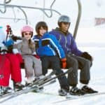 A happy smiling family are on a ski lift.