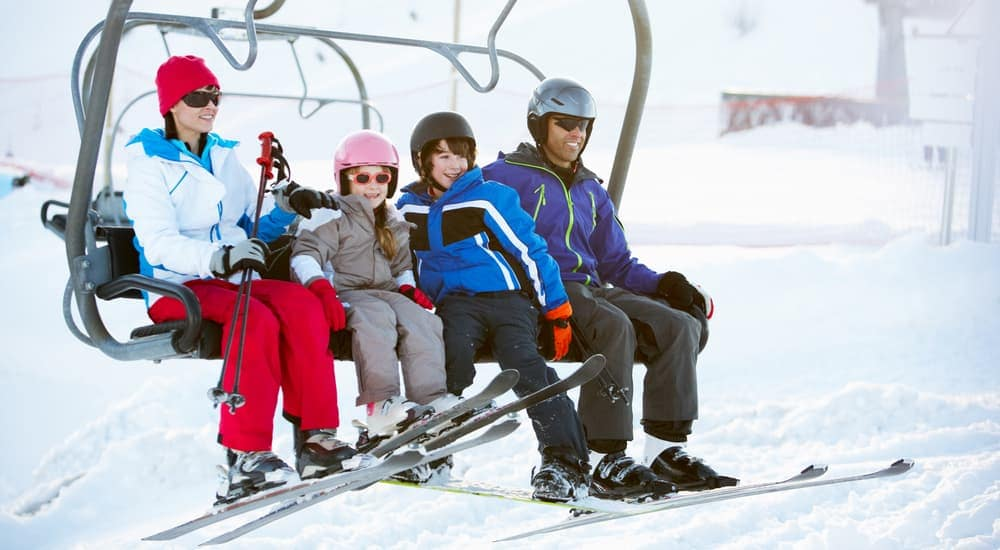 A happy family is on a ski lift on a mountain near Colorado Springs, CO.