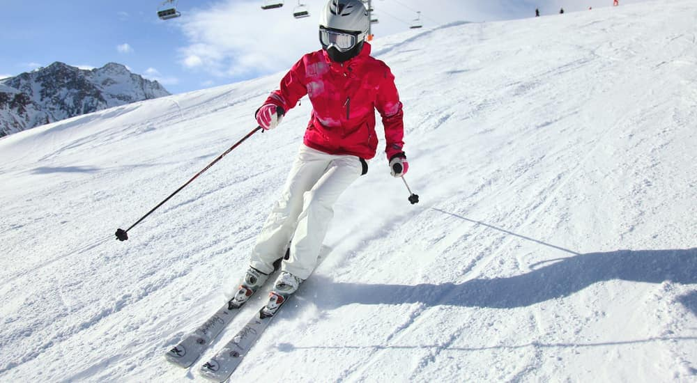 A women is skiing down a snowy trail on a sunny day.
