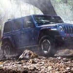 A blue 2020 Jeep Wrangler equipped with some of the best Jeep accessories for 2020 models is off-roading near Colorado Springs, CO.