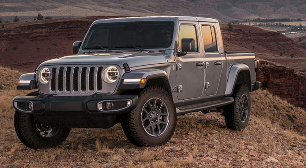A grey Jeep Gladiator is parked on a hill over looking mountains near Colorado Springs, CO.