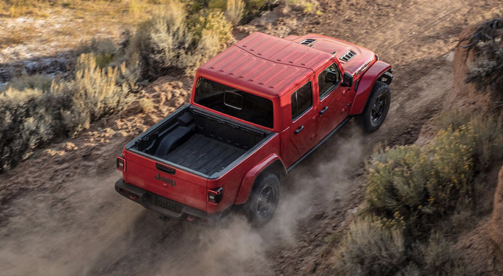 A bird's eye view of a red 2020 Jeep Gladiator, which is a popular vehicle at your local Jeep Dealership in Colorado Springs, CO, is driving up a hill off-road.