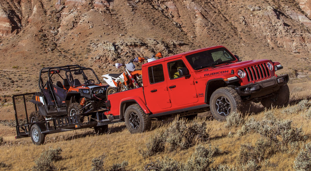 A red 2020 Jeep Gladiator is near Colorado Springs, CO while towing 2 side by sides with 2 dirt bikes in the bed.