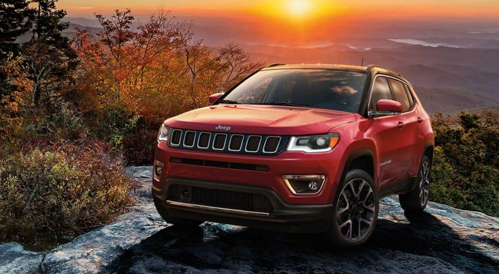 A red 2020 Jeep Compass is parked on the top of a large rock after off-roading.