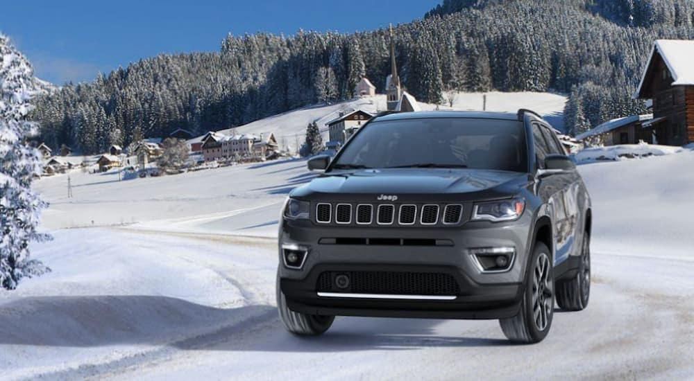A grey 2020 Jeep Compass, which is a popular option among the Jeep models, is driving on a snowy road in Colorado Springs, CO.