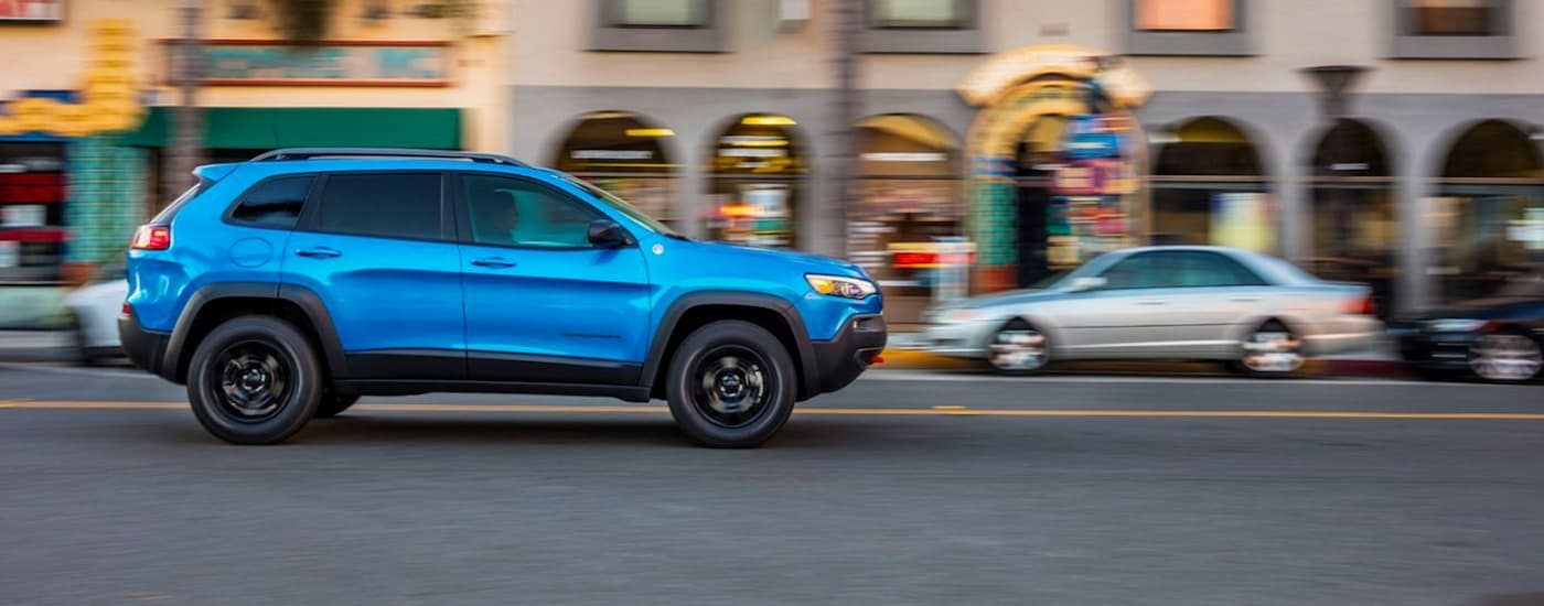 A blue 2020 Jeep Cherokee is driving on a city street.