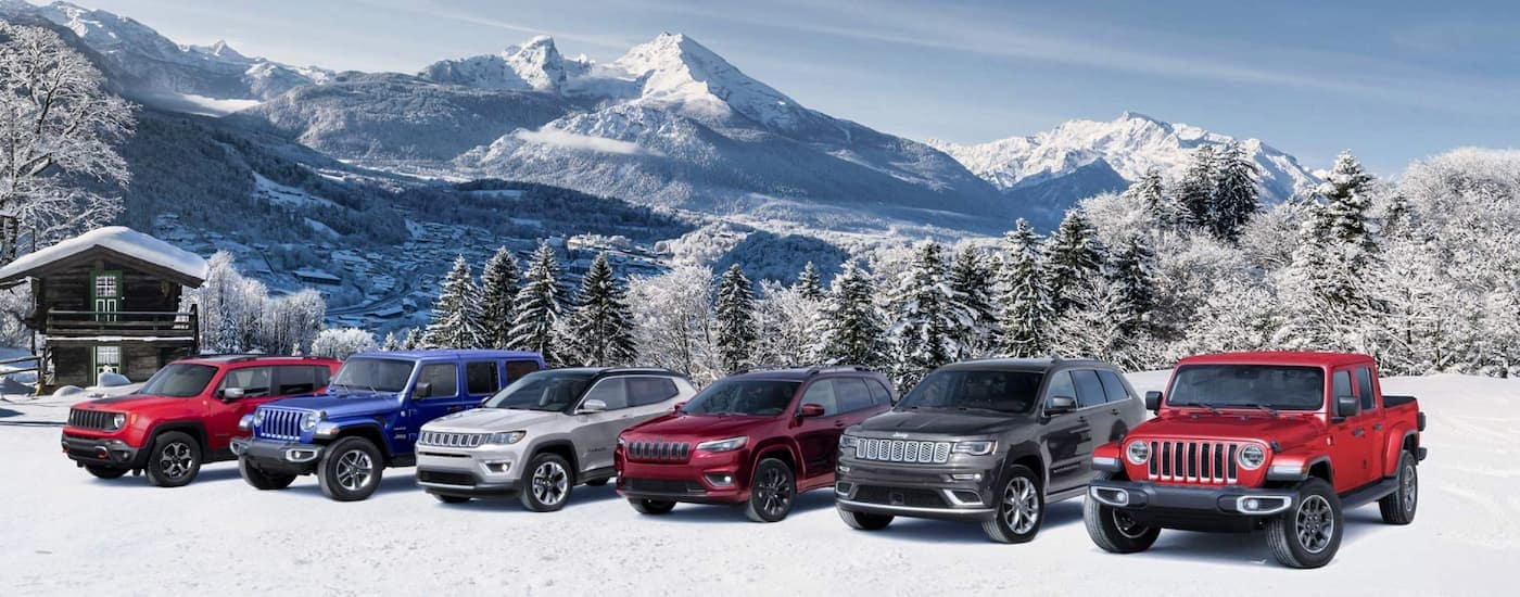 The lineup of 2020 Jeep models is shown in front of snowy mountains.