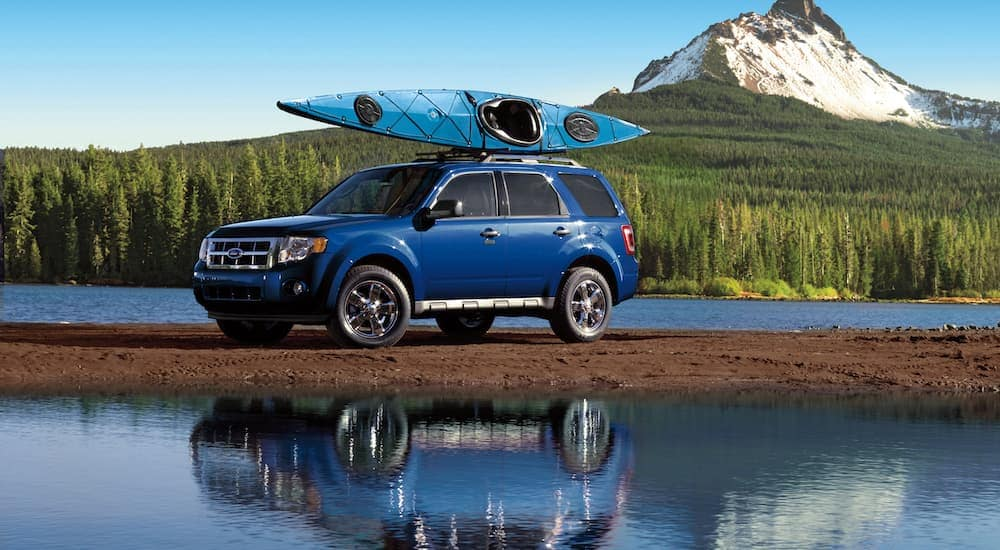 A blue 2010 Ford Escape is parked between a river and a mountain with a kayak on the roof.
