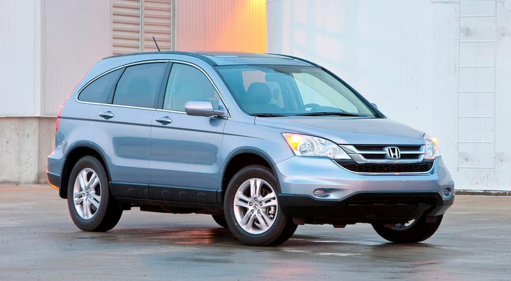A light blue 2011 Honda CR-V, popular among used cars in Colorado Springs, is parked in front of a white building.