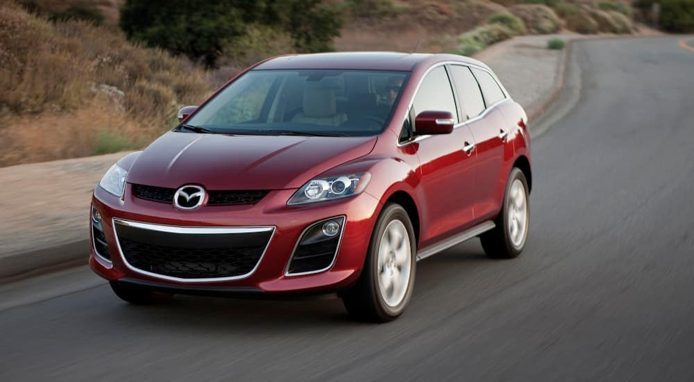 A red 2011 Mazda CX-7 is driving around a corner on a highway.