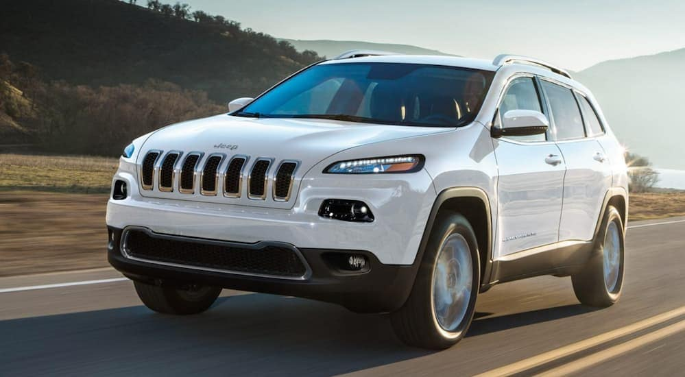 A white 2018 Jeep Cherokee, which is a popular option among used cars in Colorado Springs, CO, is driving on a road next to a lake.