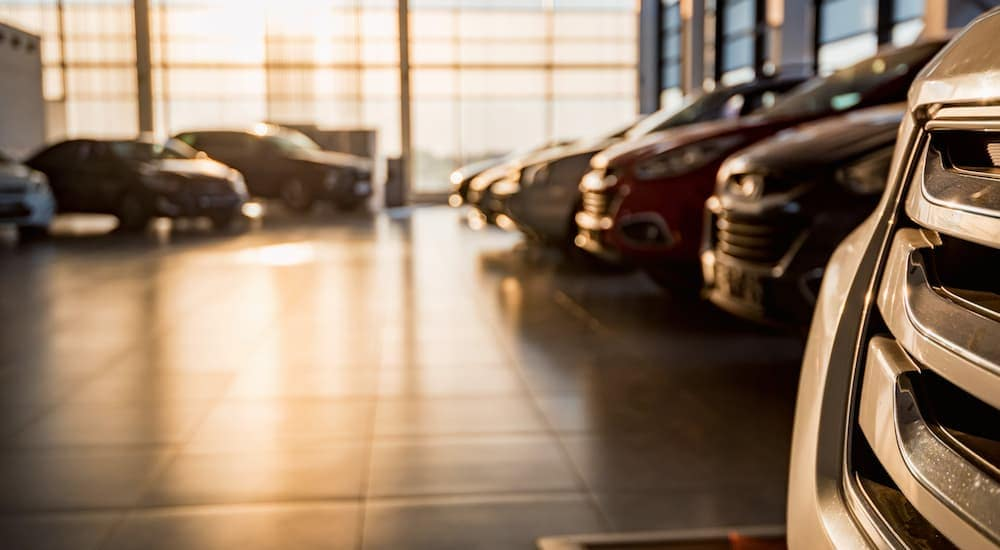 Used cars that are in a dealership showroom are shown.