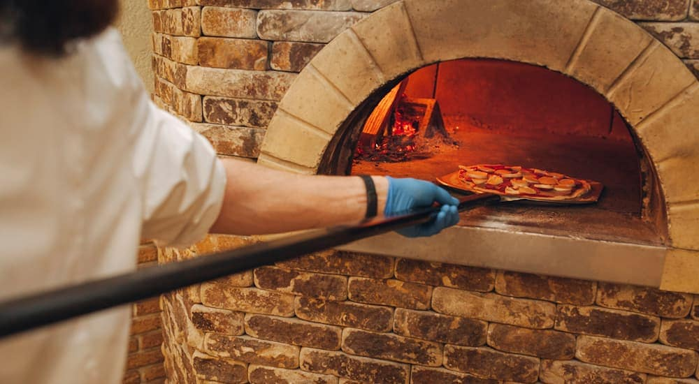 A man is pulling out a brick oven pizza out of a brick lined oven.