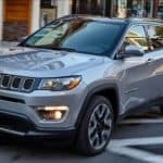 A grey 2020 Jeep Compass is driving past blurred buildings near Colorado Springs, CO.