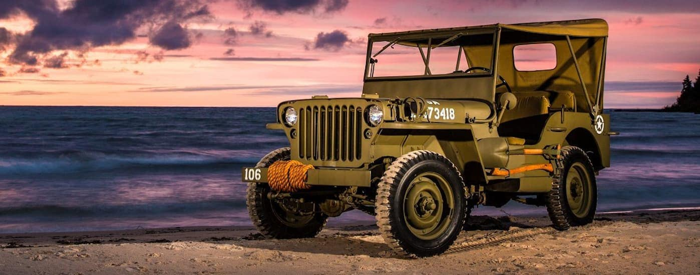 A 1940's military Jeep is parked on a beach next to the ocean at dusk.