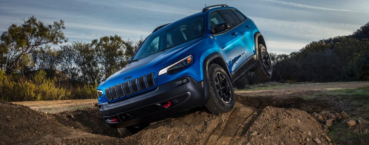 A blue 2020 Jeep Cherokee, which is a popular option among Jeep models, is off-roading through large ruts on a dirt trail.