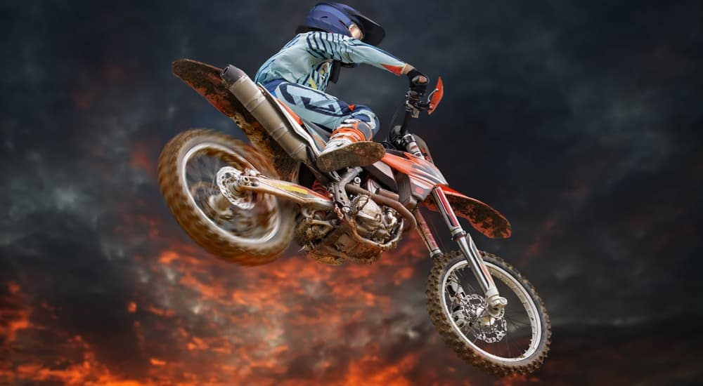 A man on a dirt bike to doing a trick in the air, similar to one you may see at Monster Jam in Colorado Springs, CO.