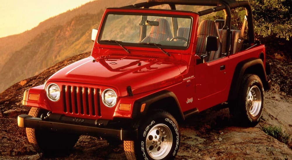 A red 1997 Jeep Wrangler TJ, which is a popular option among used cars in Colorado Springs, CO, is off-roading at dusk.