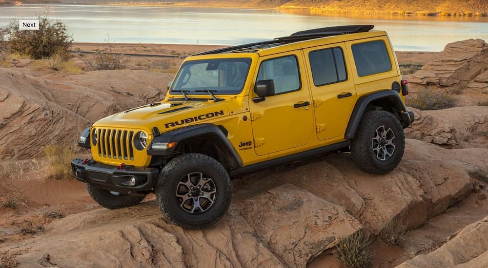 A yellow 2020 Jeep Wrangler JL 4-door is rock crawling next to a small lake.