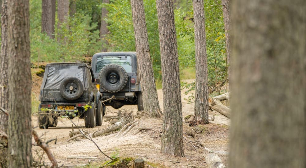 A green Jeep Wrangler YJ is towing a small SUV on a dirt trail through the woods.