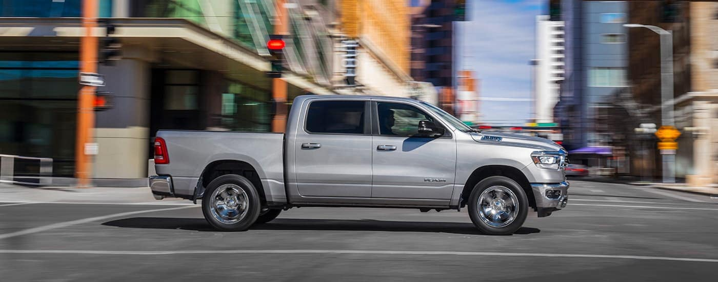 A silver 2019 Ram 1500 is driving through a city intersection.