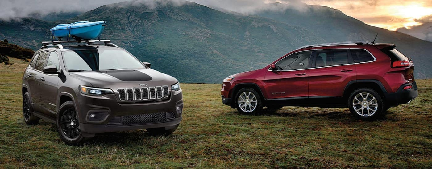 A grey 2020 Jeep Cherokee and a red Certified Pre-Owned model are parked in front of mountains.