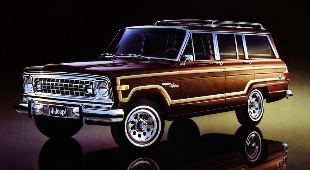 A popular Jeep model in Colorado Springs, a burgundy and wood-panel 1978 Jeep Wagoneer Limited is parked against a black background.