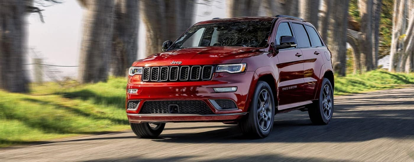 A red 2020 Jeep Grand Cherokee is driving on a country side road.
