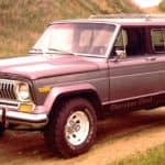 A silver 1978 Jeep Cherokee is parked on a dirt road.