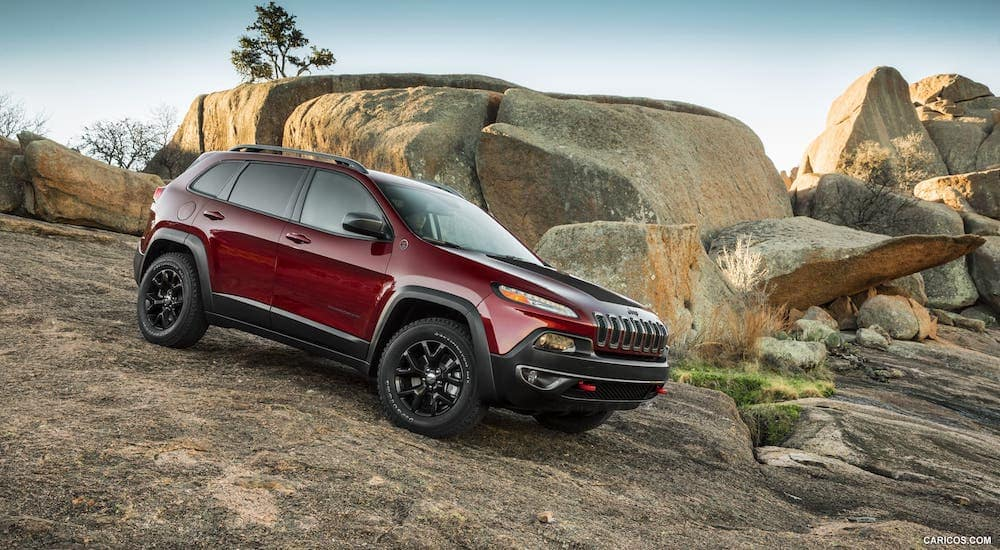 A red 2014 Jeep Cherokee Trailhawk is driving over rocks outside Colorado Springs, CO.