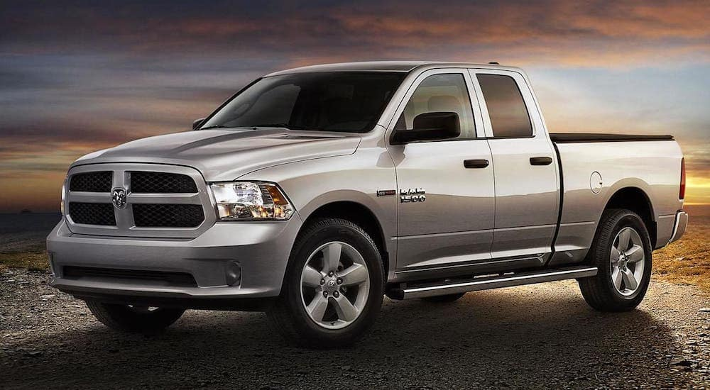 A silver 2015 Ram 1500 is parked in front of a vibrant sunset outside Colorado Springs.