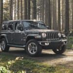 A man is walking away from his 2020 Jeep Wrangler Unlimited in the woods that he purchased from a Colorado Springs Jeep dealership.