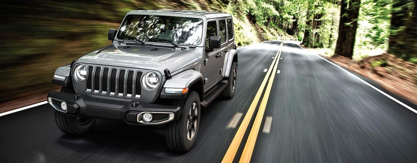 A grey 2019 Jeep Wrangler is driving on a tree-lined road near Colorado Springs, CO.