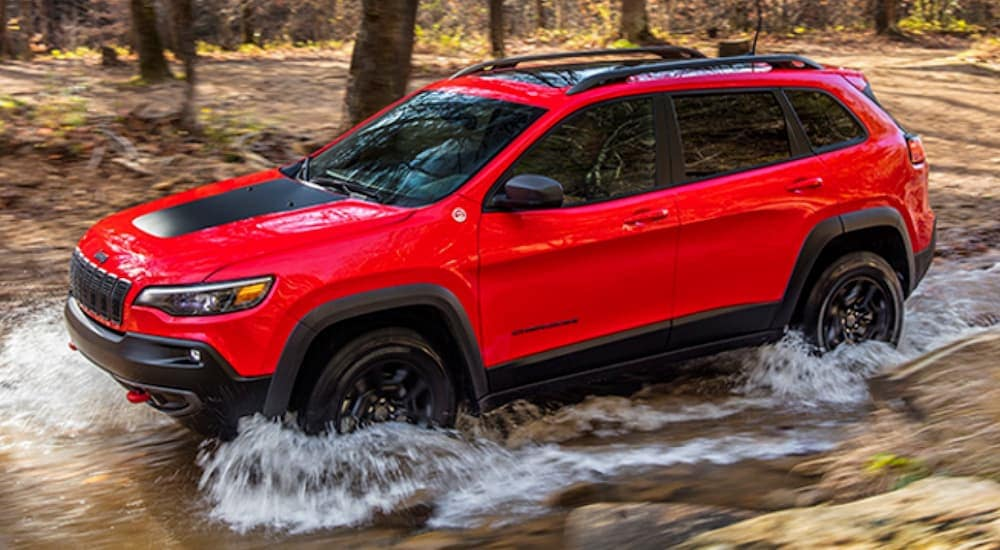 A red 2020 Jeep Cherokee Trailhawk, which is popular among Jeeps for sale in Colorado Springs, CO, is off-roading through water.